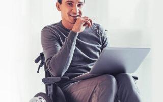 Mężczyzna na wózku pracujący przy laptopie.